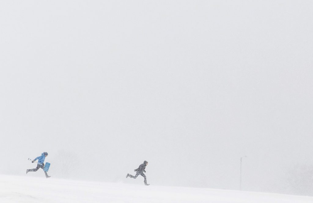 Two people run through the heavy snow in Eastern Prom park in Portland during Tuesday's nor'easter.