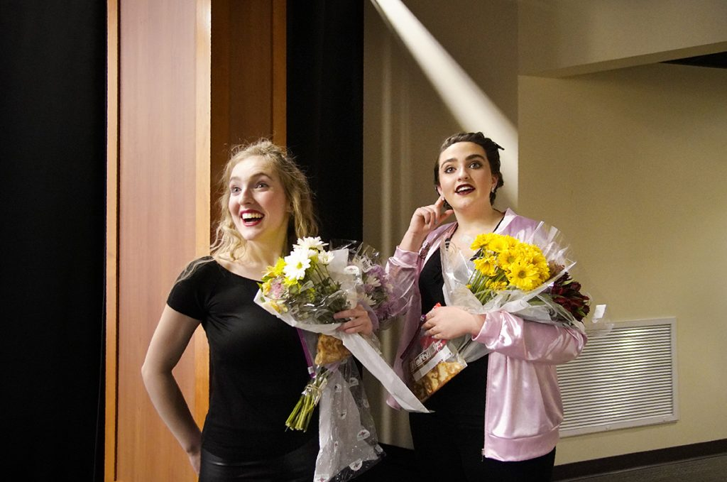 As they return backstage after the opening night performance of the musical Grease at Wells High School on  March 15, 2018, Kylie Belanger, left, and Delaney Bailey listen as people congratulate them on their performances.