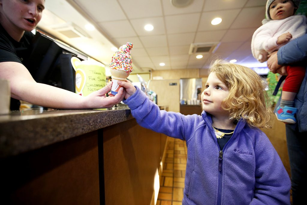 Kendra Laughlin, manager of a Dairy Queen store on Main Street in Westbrook, hands a free small ice cream cone to Emilia Lovejoy, 3, of Portland, while sister Madeline, 1, looks on. The franchise location was offering free cones to celebrate the first day of spring.