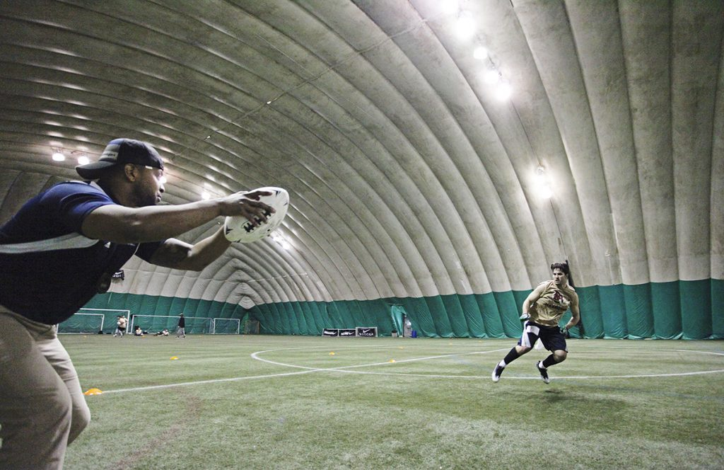 Coach Steven Barker, left, leads Logan Stewart of Hampden in a drill during local tryouts March 11 for Maine's new indoor football team, the Mammoths, at Seacoast United of Topsham.