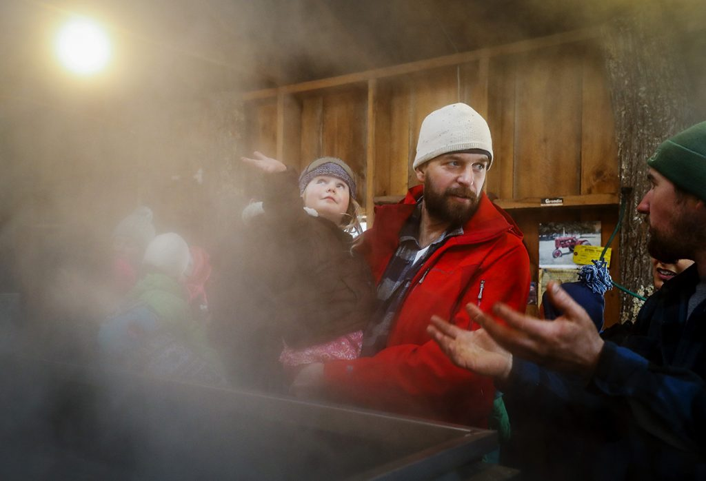 Linnea Miller, 3, left, runs her hand through the steam from the evaporator as her father Brent, center, speaks with Adam Parsons, right, during a tour of the sugar shack at Parsons Maple Products, March 25, 2018 in Gorham, for Maine Maple Sunday.