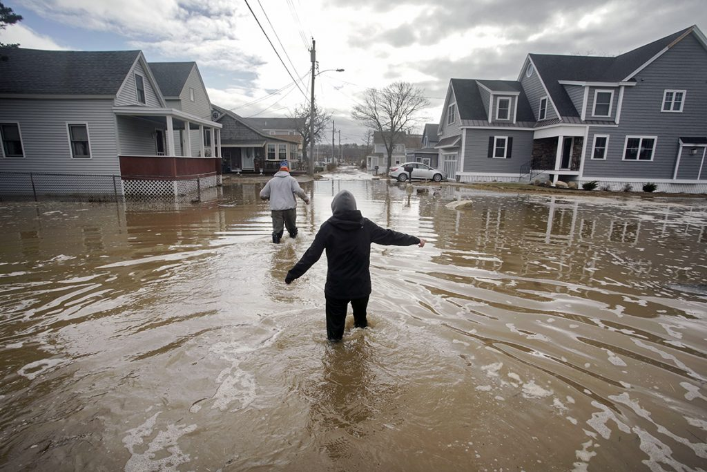 Kaylee Collin, right, and Spencer Stone walk through water along North Avenue in Camp Ellis in Saco on Sunday, March 4. The coastal neighborhood as well as other parts of the southern Maine coast were flooded for the third day in a row on Sunday.