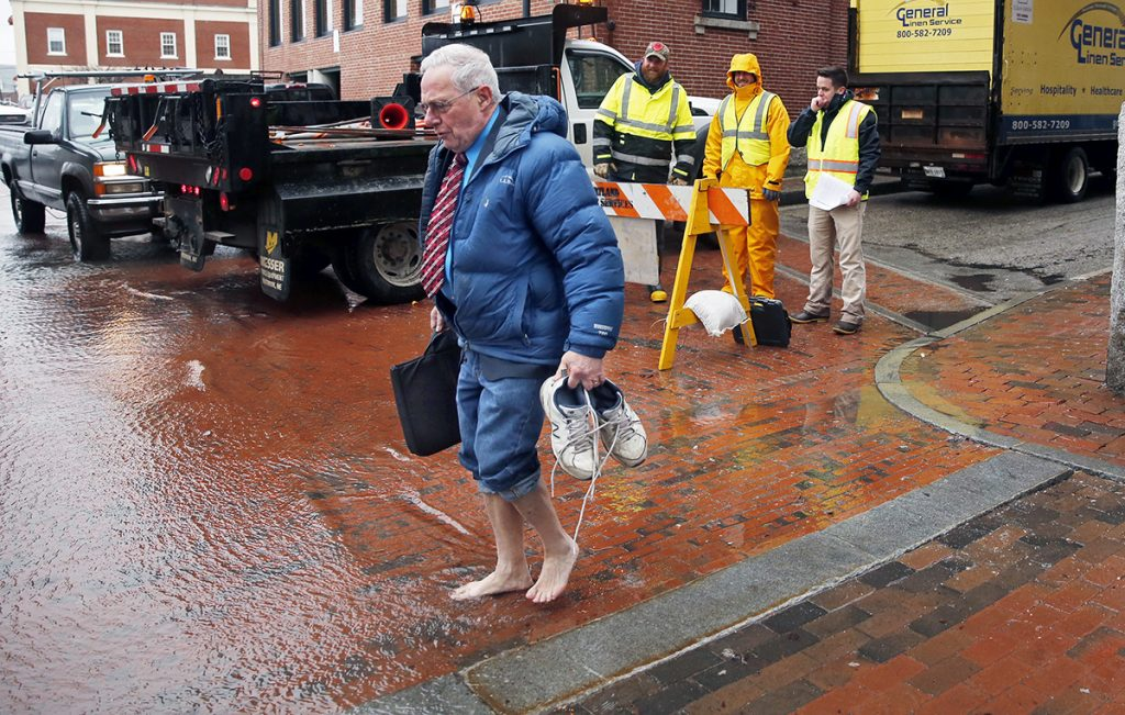 Lawyer Fred Moore prepares to enter floodwater on Portland Pier on March 2 while city employees Brian Cogill, Ryan Sullivan and Kevin Deneault look on. High winds and rain coincided with a lunar high tide, which pushed seawater against the door of Moore's office at Robinson, Kriger & McCallum.