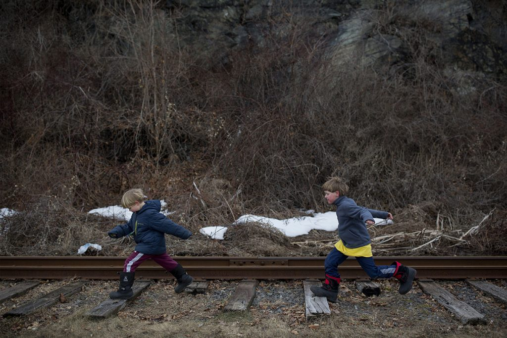 Ben Stevenson, 5, left, and his brother Schuyler Stevenson, 7, jump along the wood railroad ties on the Maine Narrow Gauge Railroad Company track on Feb. 22 in Portland.