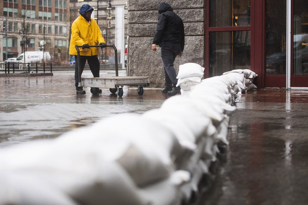 Workers place sandbags in front of the entrance to Faneuil Hall to prevent further flooding during the storm in Boston on Friday.