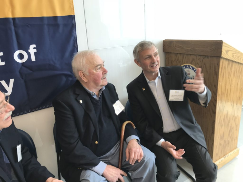 Benefactor Ray Stevens, right, and his onetime mentor, Professor Emeritus of Chemistry John Ricci, share a moment during Friday's 10-year celebration of the John Ricci Undergraduate Fellowship at the University of Southern Maine's Science Building in Portland.