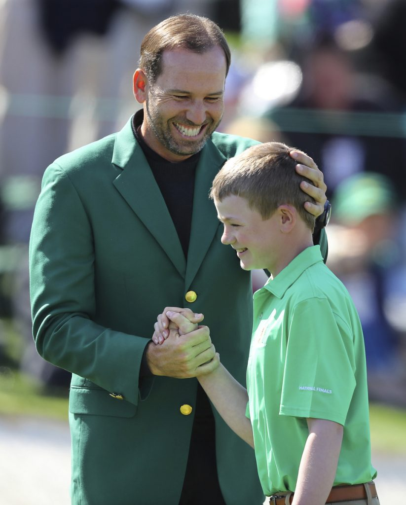 Sergio Garcia, the defending Masters champion, greets Nicholas Gross of Downington, Pa., after Gross' shot on the 18th green won the putting title for his age group Sunday.