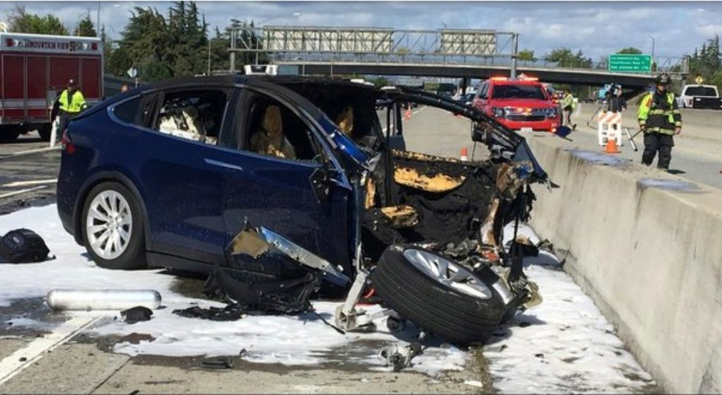 Emergency personnel work at the scene where a Tesla electric SUV crashed into a barrier on Highway 101 in Mountain View, Calif., on March 23, killing the driver.