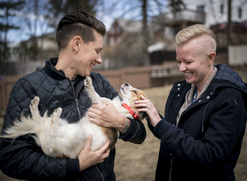 LK Weiss, left, and her wife, Laura Kloosterman, play with Duck in their yard in Bayside. They adopted her from the Animal Refuge League of Greater Portland, which has accepted hundreds of dogs from the island.