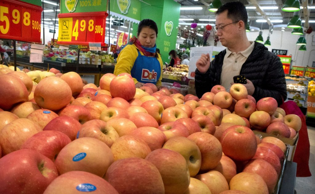 A woman wearing a uniform with the logo of an American produce company helps a customer shop for apples in a supermarket in Beijing. China raised import duties on a $3 billion list of U.S. pork, fruit and other products Monday.