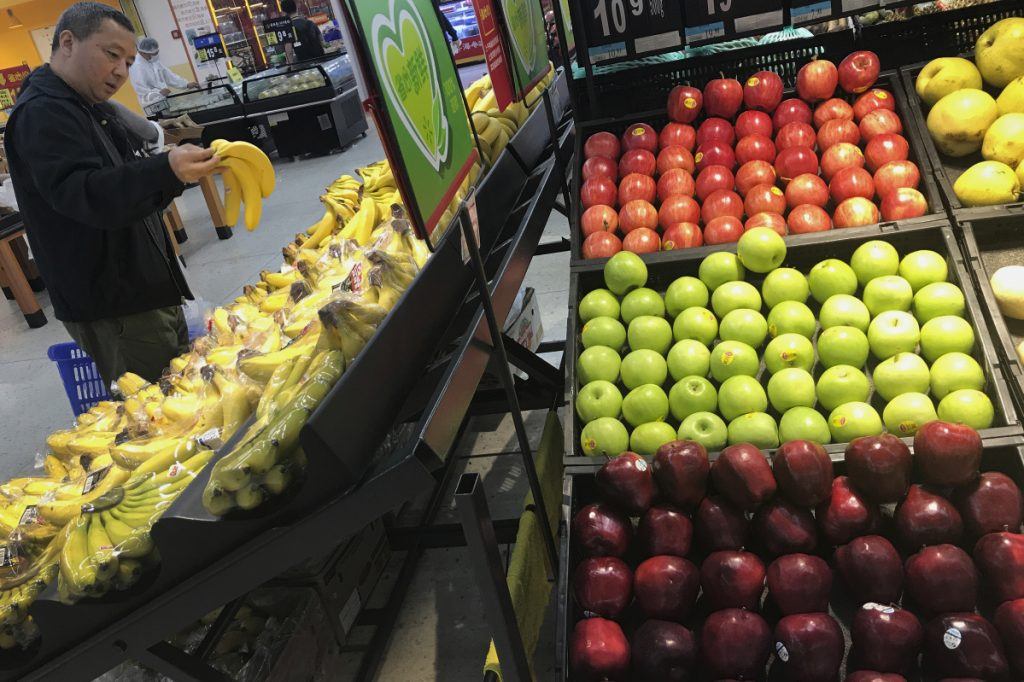 A man chooses bananas near imported apples from the United States at a supermarket in Beijing on Monday