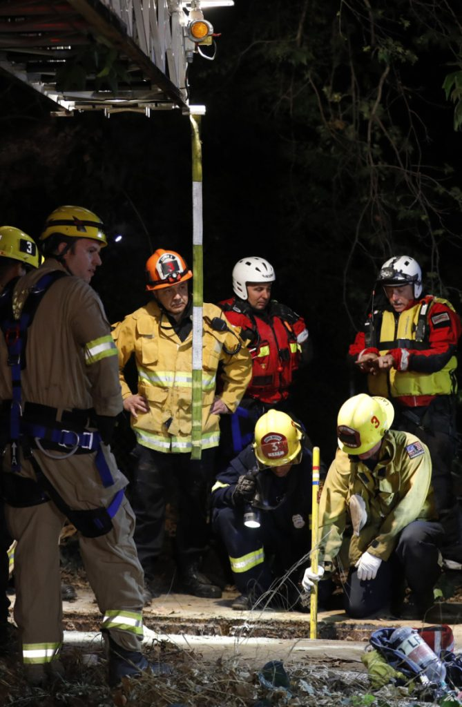 Firefighters search for a 13-year-old boy in a hole Sunday in Los Angeles. The boy was found alive early Monday following a frantic, 12-hour search.