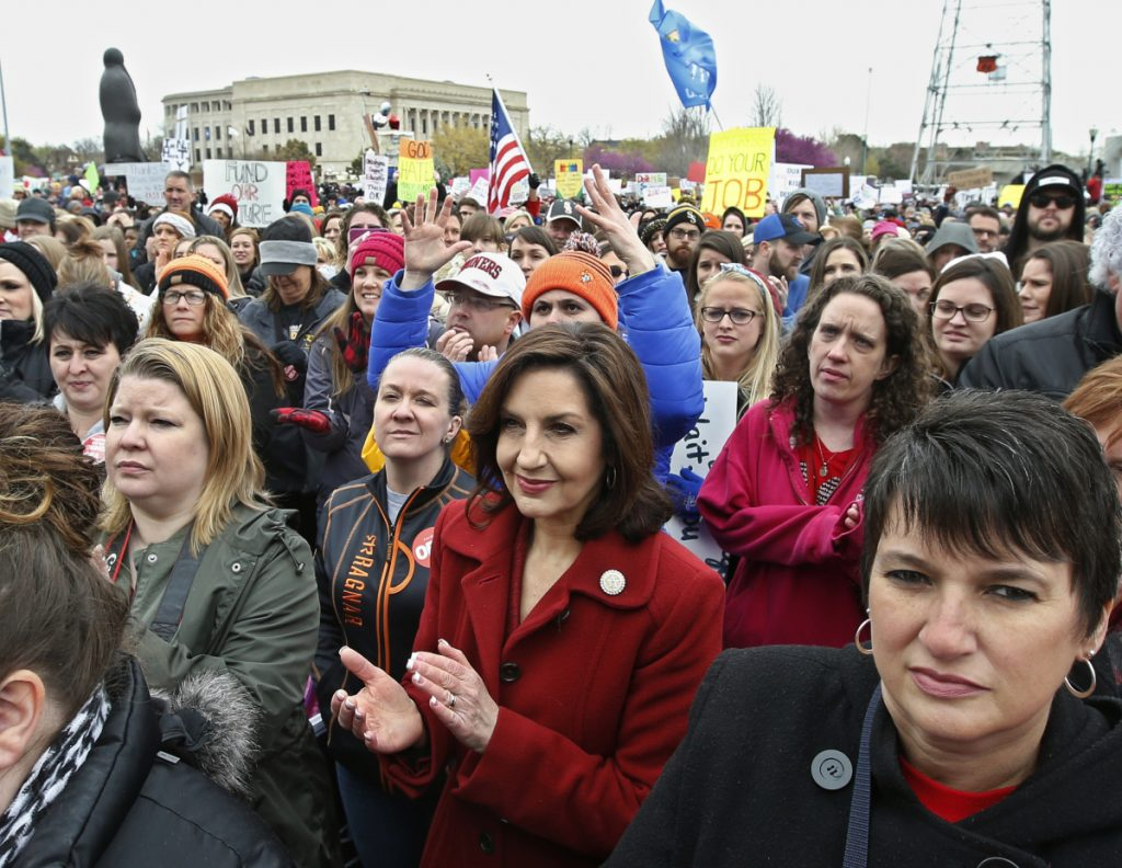 Oklahoma's State Superintendent of Public Instruction Joy Hofmeister, center, applauds during a rally in Oklahoma City. Oklahoma teachers walked out for a second day Tuesday.