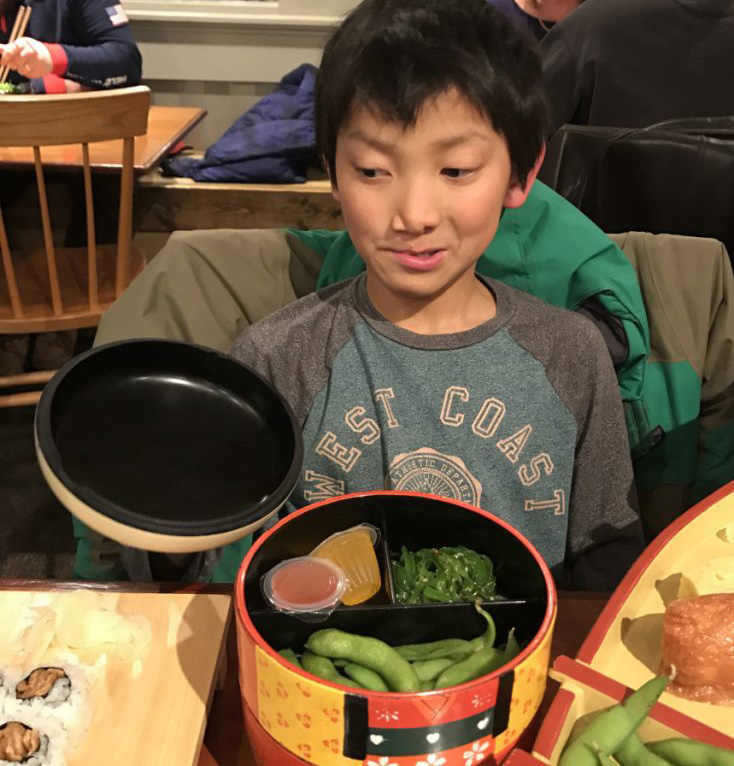 Peter Ericson, 9, brings his best side-eye game to Yosaku, glancing doubtfully at some sushi.
