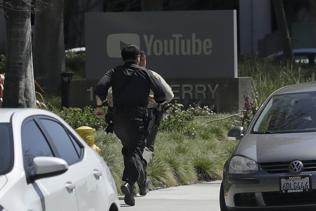 Officers run toward a YouTube office in San Bruno, Calif., on Tuesday. Police said they were responding to an active shooter there.
