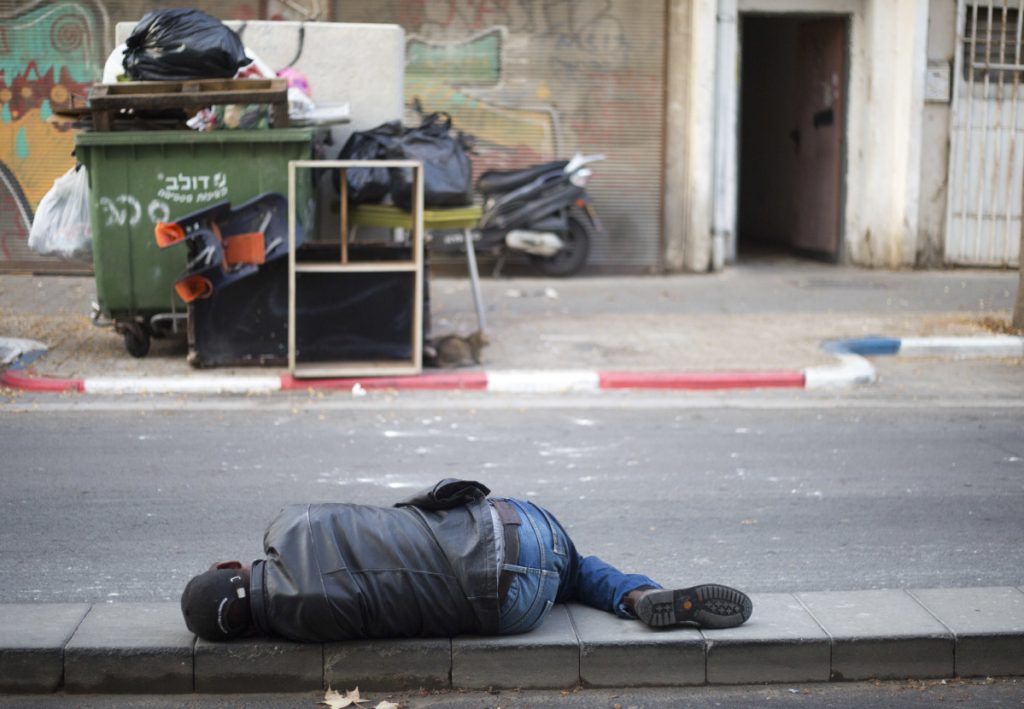 An African migrant sleeps in a street in Tel Aviv, Israel. Prime Minister Netanyahu canceled his plan to help resettle migrants.