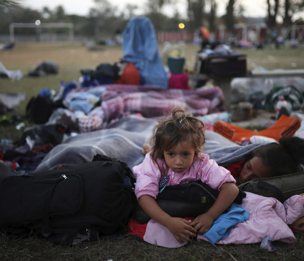"A girl remains awake as Central American migrants traveling with the annual ""Stations of the Cross"" caravan sleep at a sports club in Matias Romero, Mexico, on Tuesday."