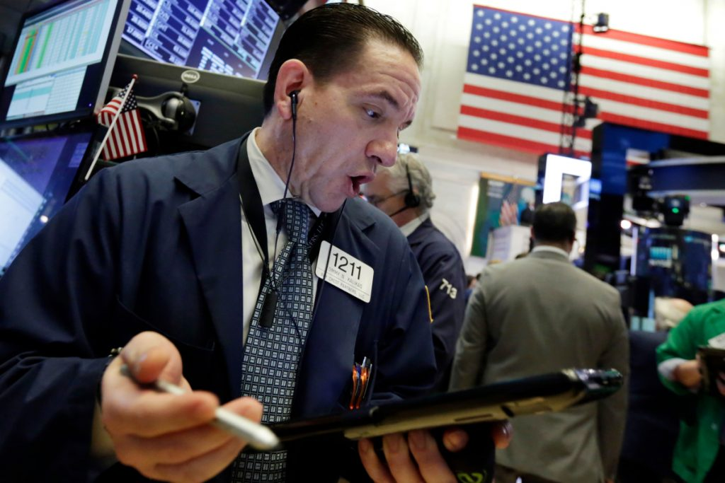 Trader Tommy Kalikas works the floor in New York early Wednesday, when China's retaliation for new U.S. tariffs sent stocks plunging. But the Dow ended up rising 231 points for the day.
