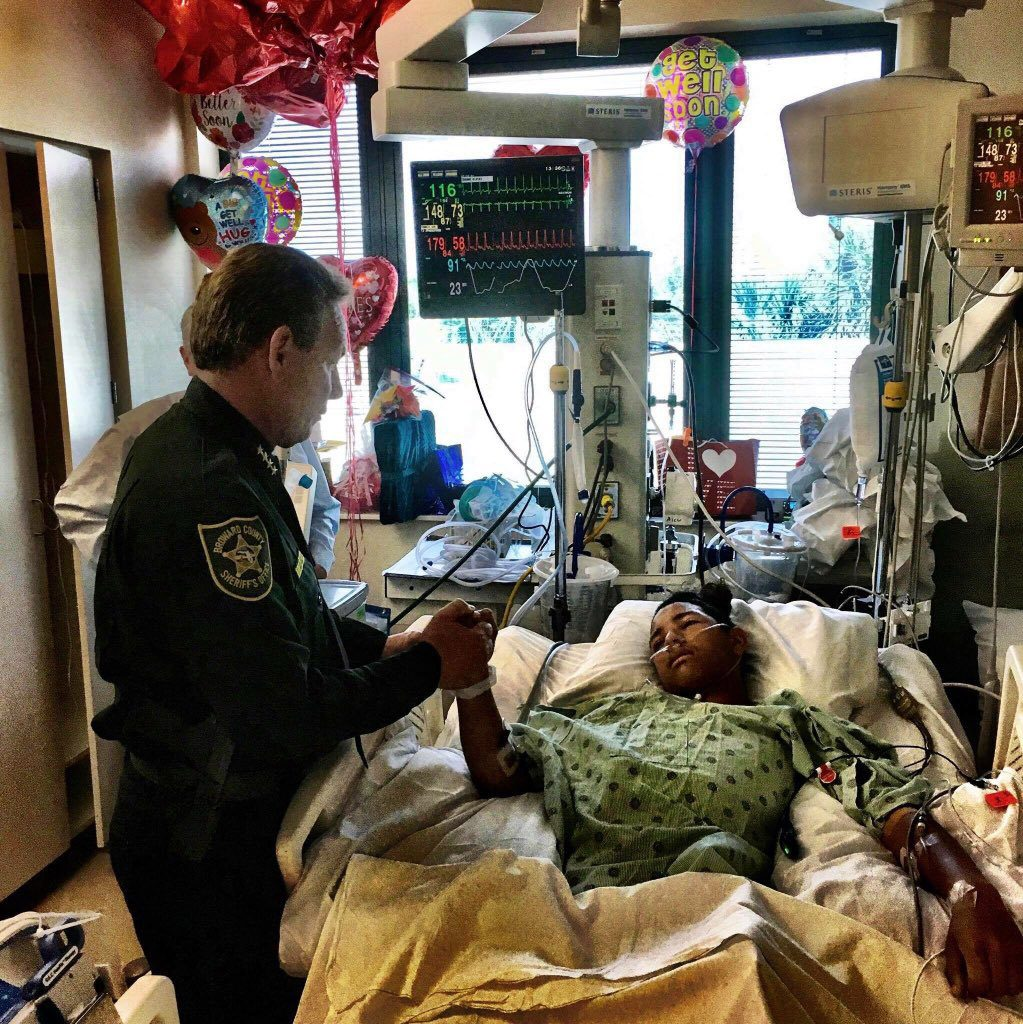Broward County Sheriff Scott Israel holds the hand of 15-year-old Parkland survivor Anthony Borges on Feb. 18.