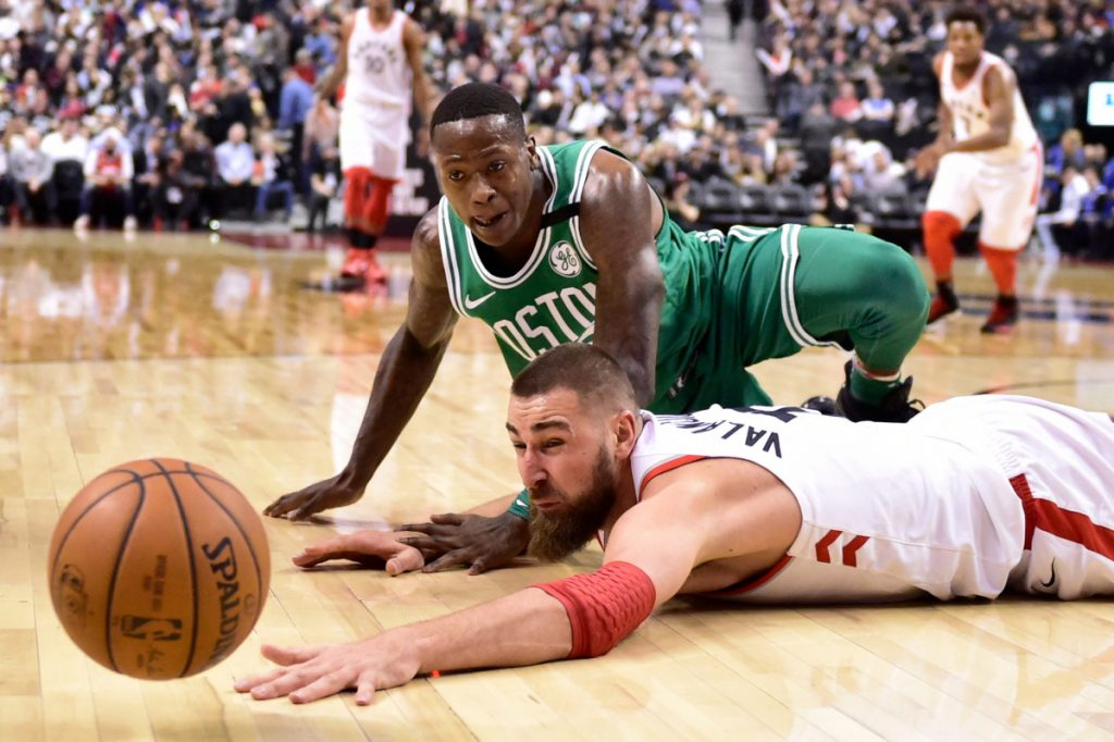 Toronto's Jonas Valanciunas and Boston's Terry Rozier fall to the floor chasing a loose ball in the second half Wednesday at Toronto.