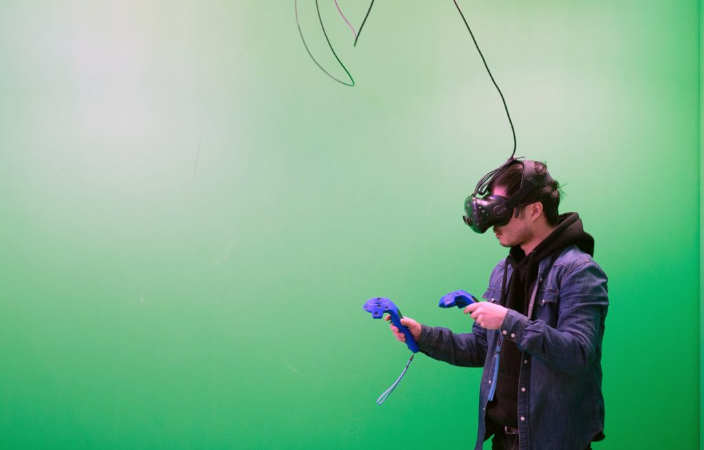 A customer wears a HTC Vive virtual-reality headset during a green-screen experience at Toronto's House of VR. Despite Hollywood funding and top industry talent, cinematic VR has yet to yield commercial success or popular acceptance.