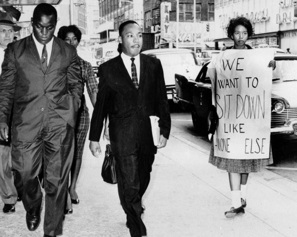 African Americans continue to struggle to attain economic, educational and social equality, decades after the far more successful efforts to end overt discrimination, such as the lunch counter sit-ins for which Martin Luther King Jr., center, was arrested by Atlanta Police Capt. R.E. Little, left rear, in October 1960. With the minister are Lonnie C. King (no relation), a college student and protest organizer; another student demonstrator, Marilyn Pryce, center rear, and an unidentified woman.