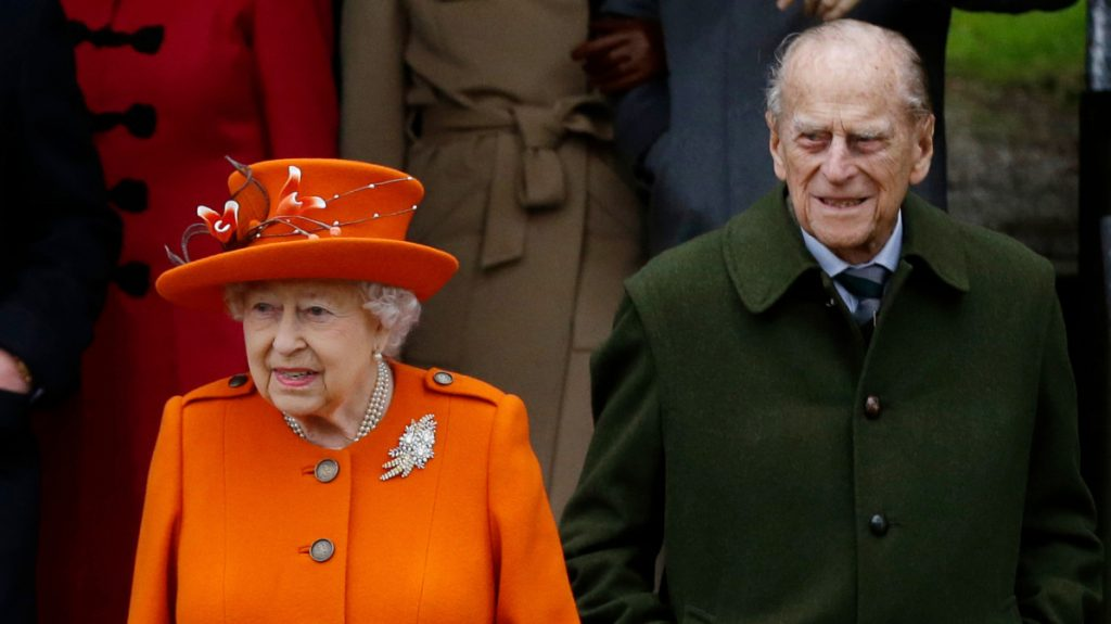 Queen Elizabeth II and Prince Philip wait for their car after a Christmas Day church service in Sandringham, England.