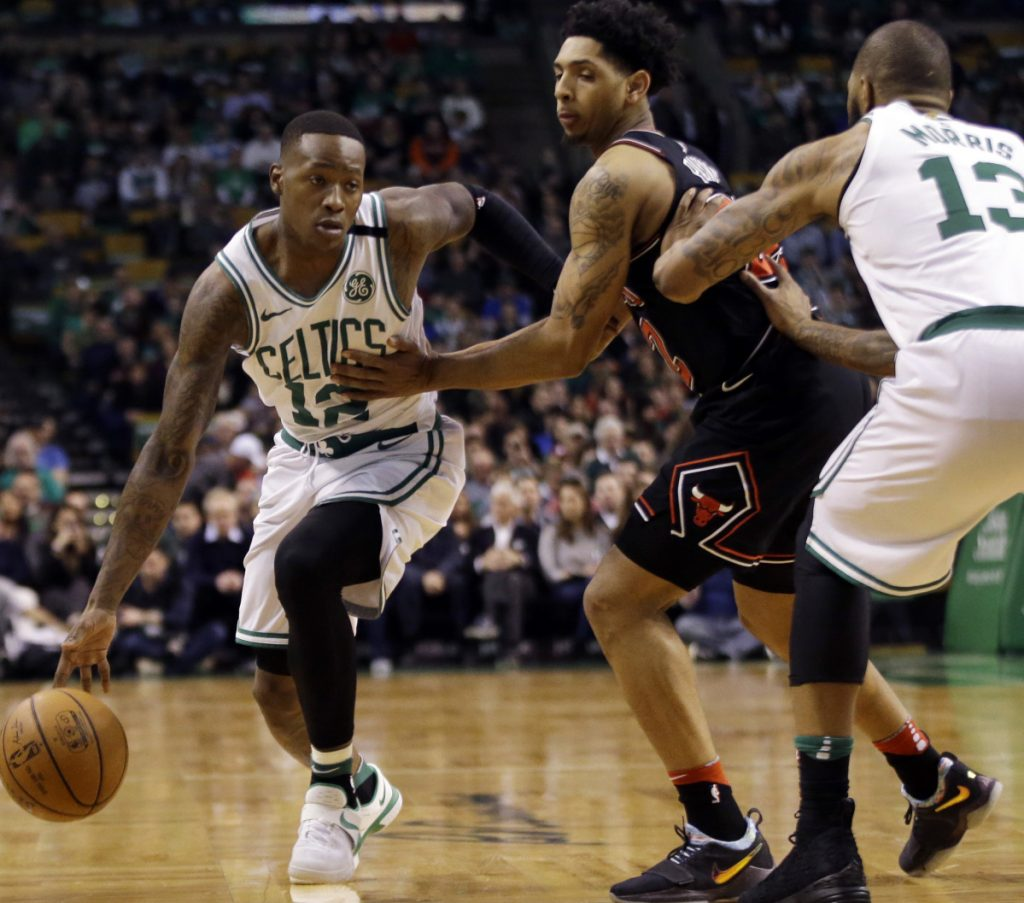 Terry Rozier of the Boston Celtics finds room to drive against Cameron Payne of the Chicago Bulls as Marcus Morris of Boston sets a pick in the first half Friday night.