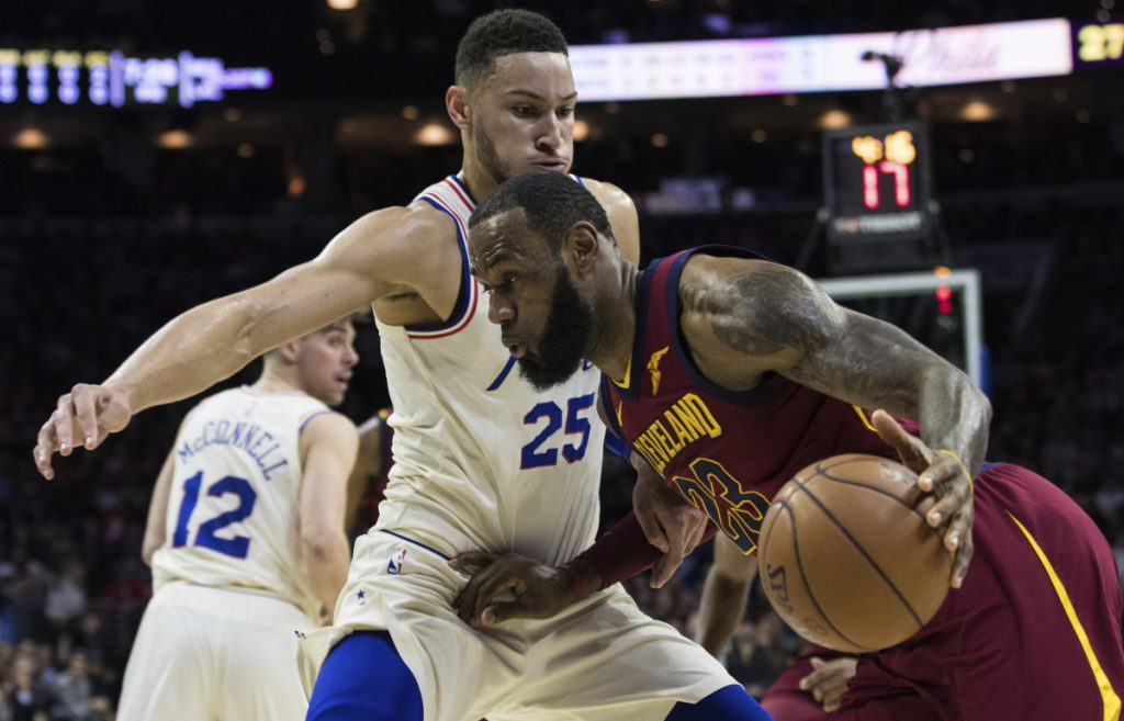 LeBron James of the Cleveland Cavaliers drives to the basket Friday night against Ben Simmons of the Philadelphia 76ers during the first half of Philadelphia's 132-130 victory – its 13th straight.