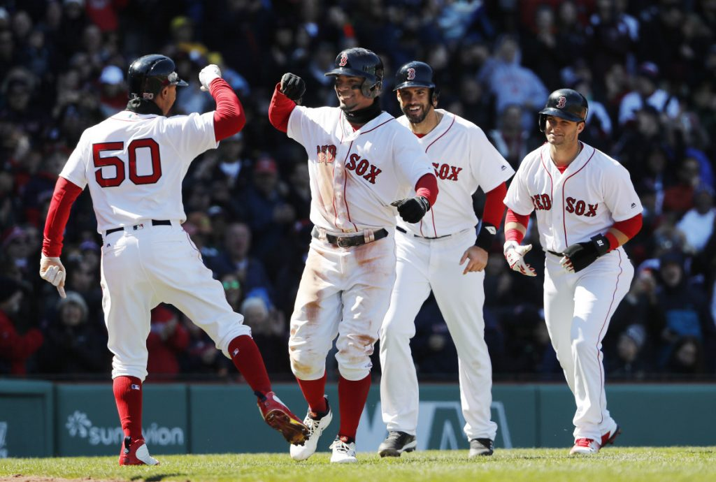 Xander Bogaerts, second from left, smiles as he is congratulated by Mookie Betts, left, after hitting a grand slam that scored Betts, Andrew Benintendi, right, and J.D. Martinez, second from right, in the second inning Saturday against the Tampa Bay Rays at Fenway Park in Boston.