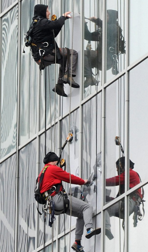 Workers remove an advertisement from a glass facade of a building  in Warsaw, Poland. A tight labor market is jeopardizing the European Union's largest eastern economy.