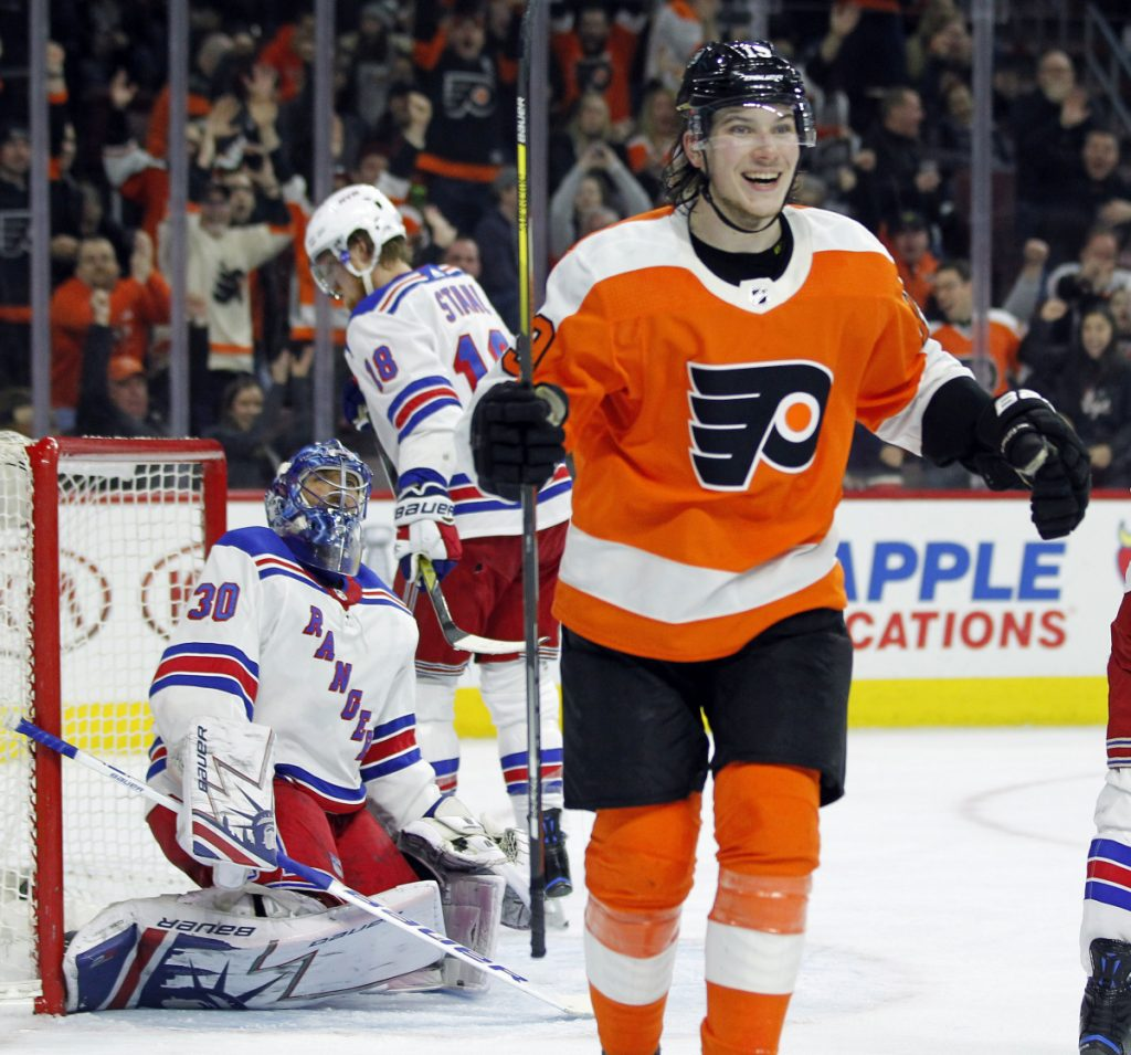 Nolan Patrick of the Philadelphia Flyers smiles Saturday while skating to congratulate Claude Giroux, who scored during the second period of a 5-0 victory against the New York Rangers. Giroux finished with three goals.