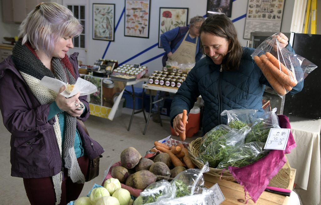 Tesse Rau of Augusta, left, buys carrots Tuesday from farmer Dalziel Lewis of China at the farmers market in Augusta.