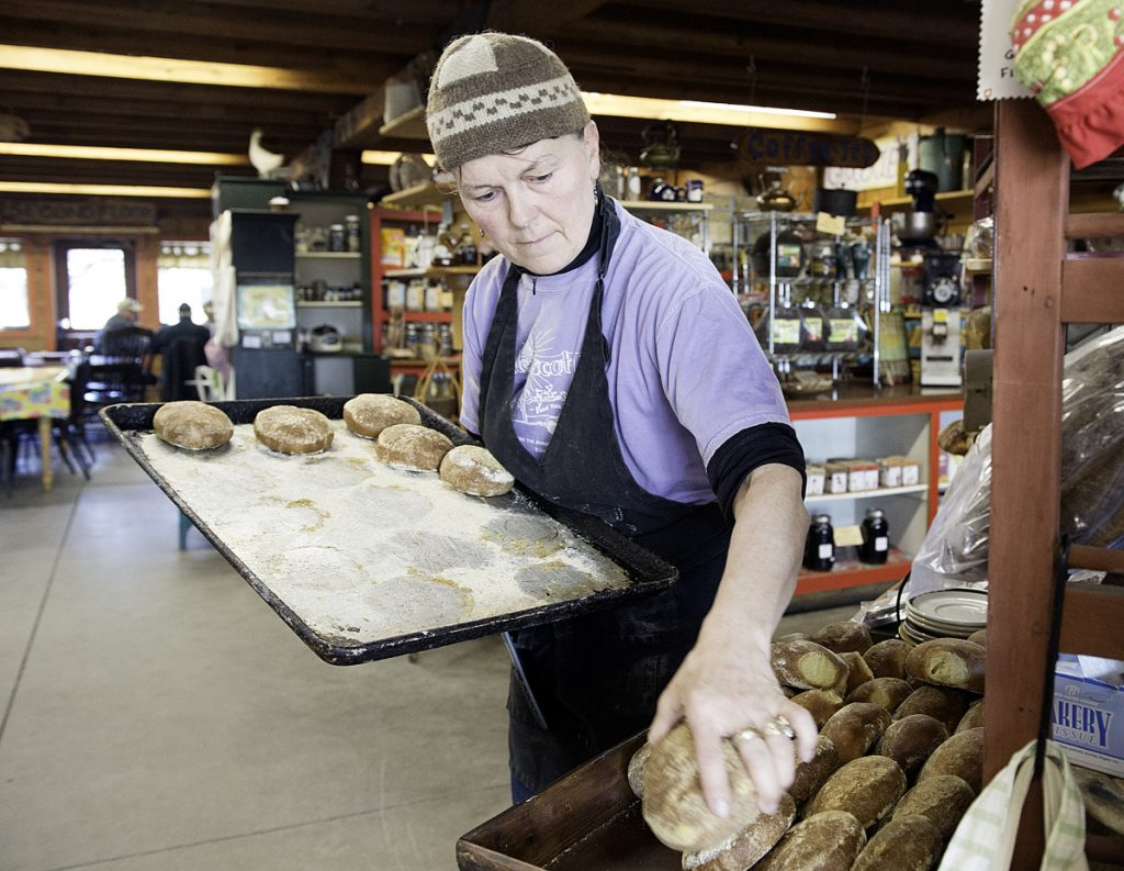 Gloria Varney puts out fresh-baked dinner rolls at Nezinscot Farm in Turner. Varney offers what she calls a