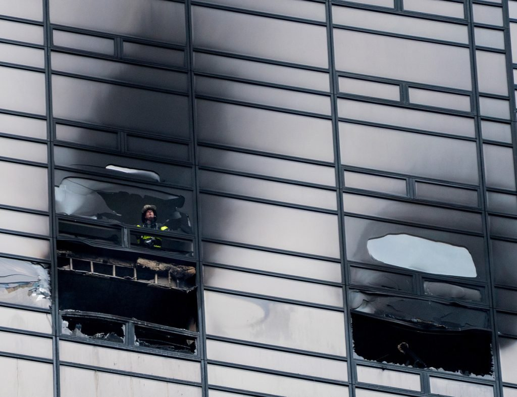 A firefighter looks out the window of a Trump Tower apartment where a 66-year-old art collector who spent time with Andy Warhol was killed in a fire.