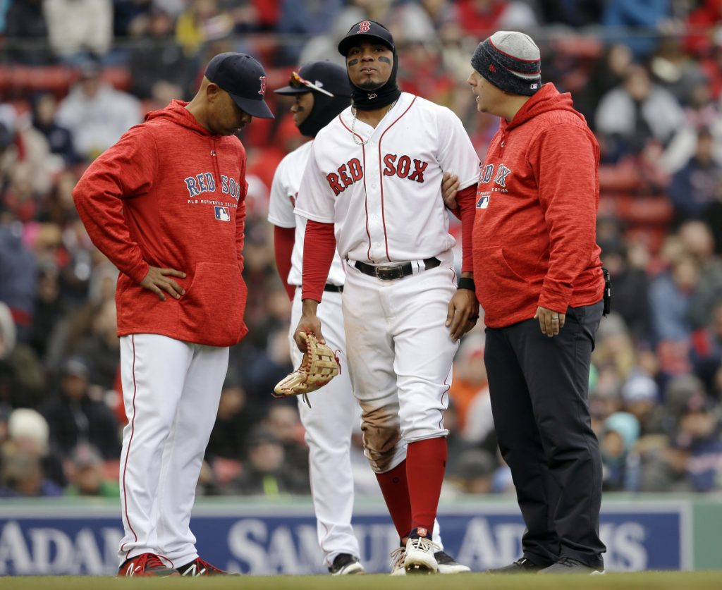 Xander Bogaerts of the Boston Red Sox limps off the field Sunday as Manager Alex Cora, left, looks on. Bogaerts injured his left ankle while sliding for an errant ball.