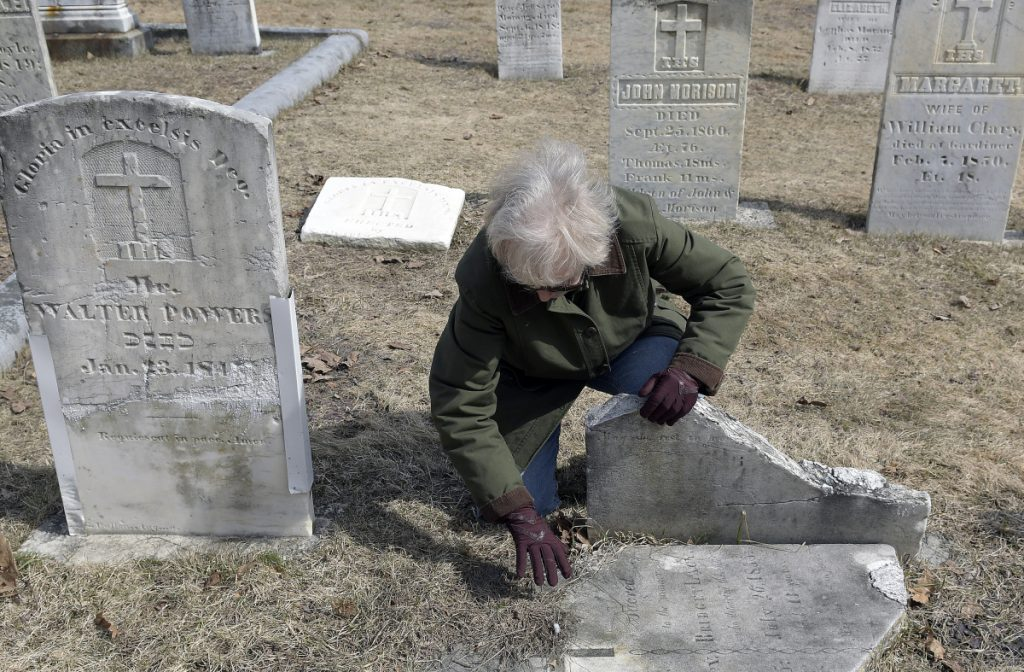 Whitefield archivist Libby Harmon uncovers the headstone of an Irish immigrant at St. Denis Cemetery in Whitefield.