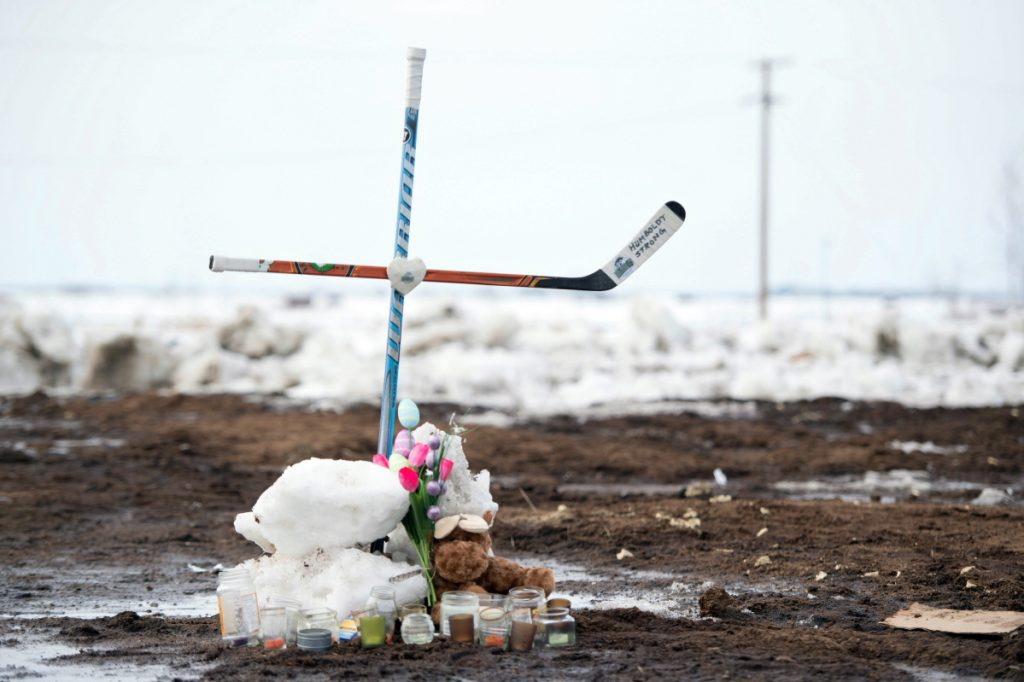 A memorial, including a cross made out of hockey sticks, sits near the intersection of a fatal bus crash near Tisdale, Saskatchewan, Canada, on Monday. A bus carrying the Humboldt Broncos junior hockey team collided with a truck Friday night, killing 15 and sending over a dozen more to the hospital.