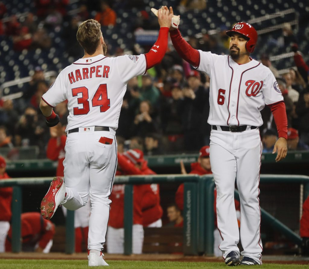 Bryce Harper of the Washington Nationals is greeted by teammate Anthony Rendon after they scored Monday night on a double by Howie Kendrick during the first inning of a 2-0 victory against the visiting Atlanta Braves.