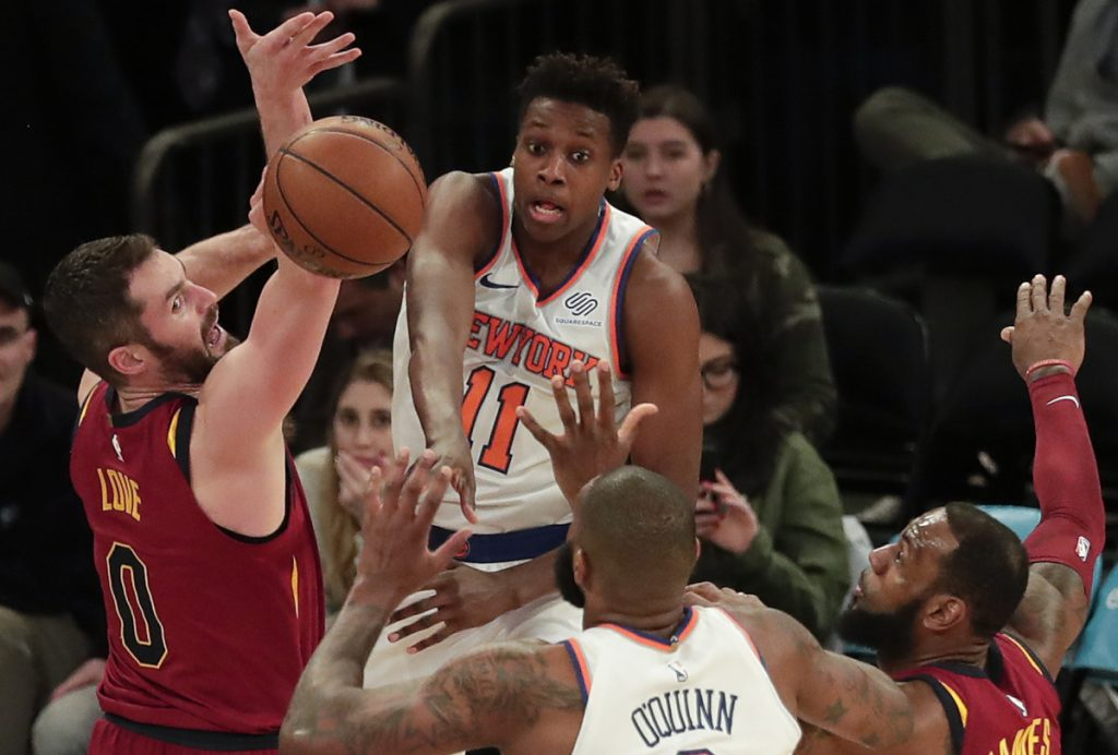 Knicks guard Frank Ntilikina makes a pass to center Kyle O'Quinn while being defended by Cleveland's Kevin Love, left, and LeBron James, right, on Monday in New York.