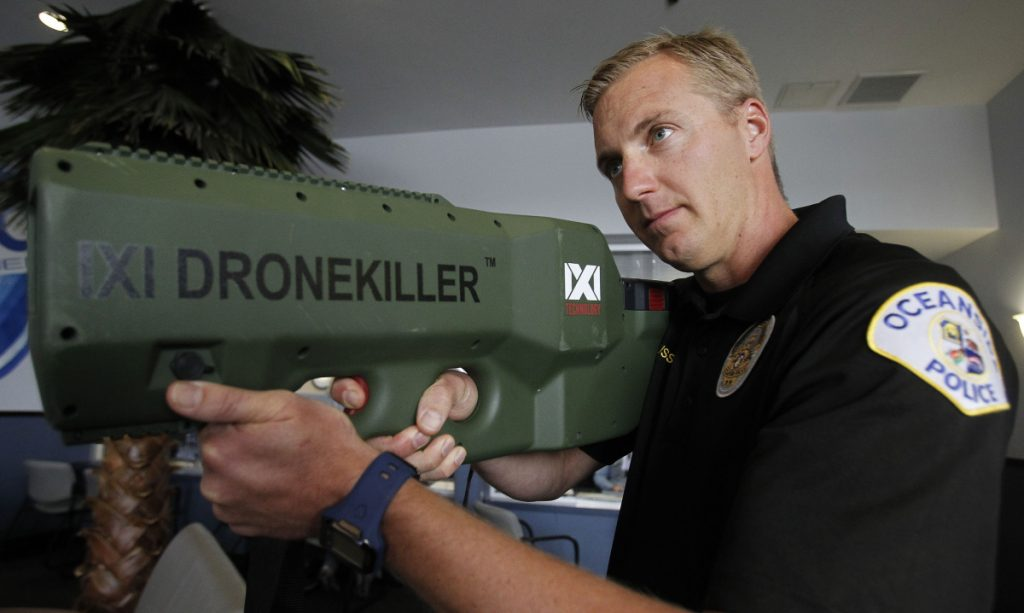 "Oceanside Police Officer Mark Bussey aims the ""drone killer,"" which brings a drone back to the ground by hitting it with radio waves that break the connection."