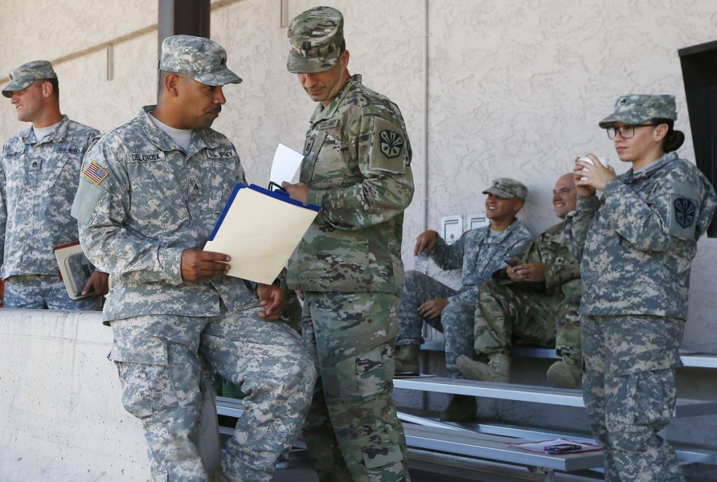 Arizona National Guard soldiers receive their reporting paperwork prior to deployment to the Mexico border at the Papago Park Military Reservation, Monday in Phoenix.