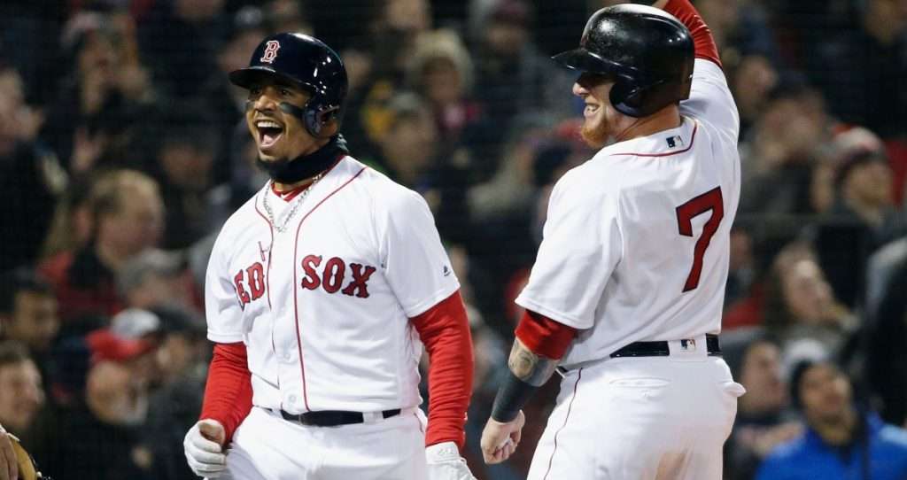 Boston Red Sox's Mookie Betts left celebrates with Christian Vazquez after scoring on a triple by Andrew Benintendi during the second inning of a baseball game against the New York Yankees in Boston Tuesday
