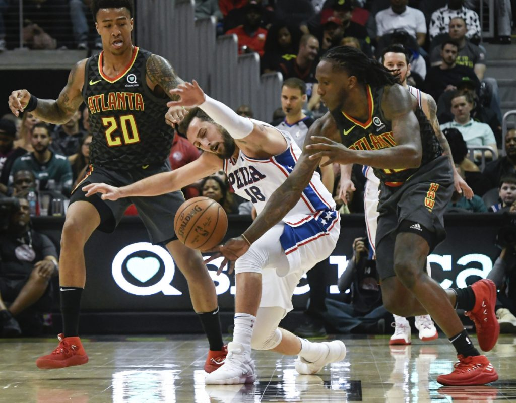 Philadelphia's Marco Belinelli has the ball stolen by Atlanta's Taurean Prince right as John Collins looks on during the second half Tuesday night in Atlanta