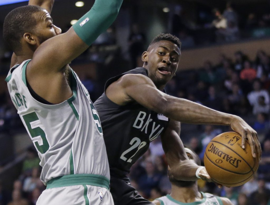 Nets guard Caris LeVert passes the ball around Celtics center Greg Monroe during Boston's 110-97 win on the final night of the regular season Wednesday.