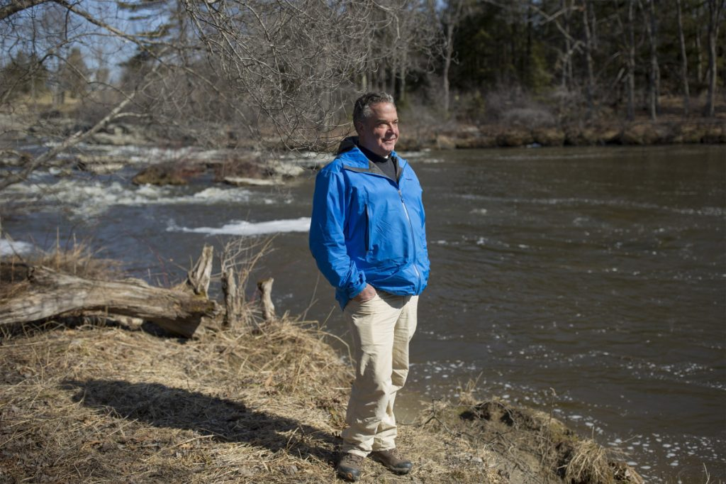Alan Stearns stands next to the Royal River in Yarmouth.