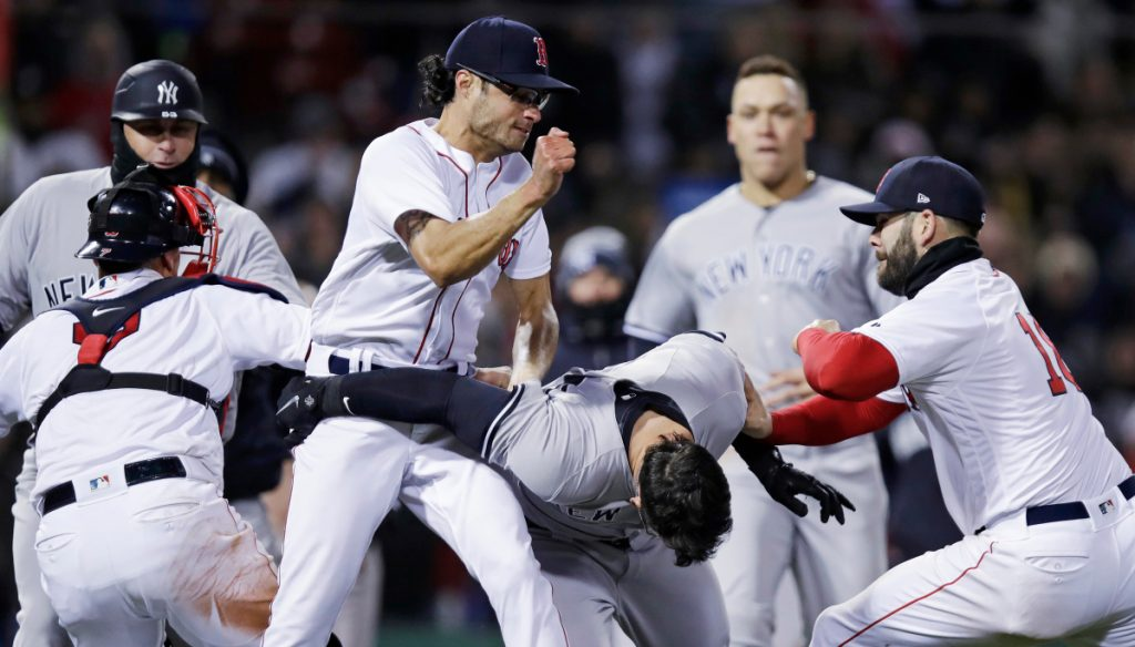 Boston Red Sox relief pitcher Joe Kelly, left, throws a punch at New York Yankees' Tyler Austin, center, as they fight during the seventh inning of Wedesday night at Fenway Park in Boston. Kelly has been suspended six games and Austin five.
