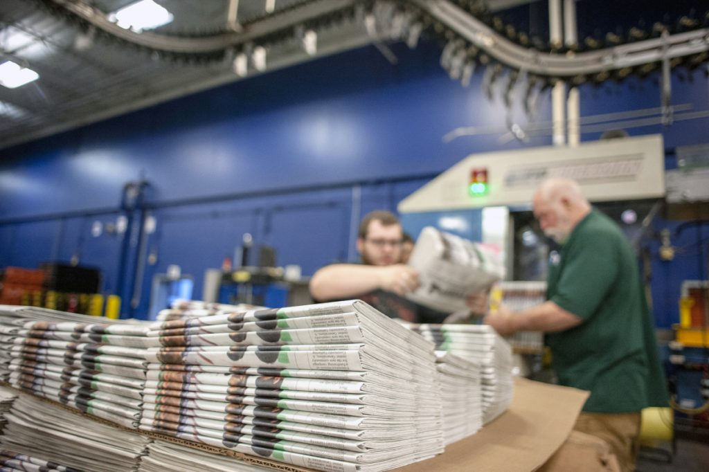 Production workers stack newspapers onto a cart at the Janesville Gazette Printing & Distribution plant in Janesville, Wis., earlier this week.