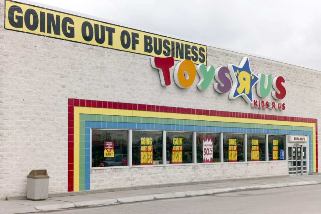 "A ""Going Out Of Business"" sign hangs over the Toys R Us store logo in Omaha, Neb., on Monday."