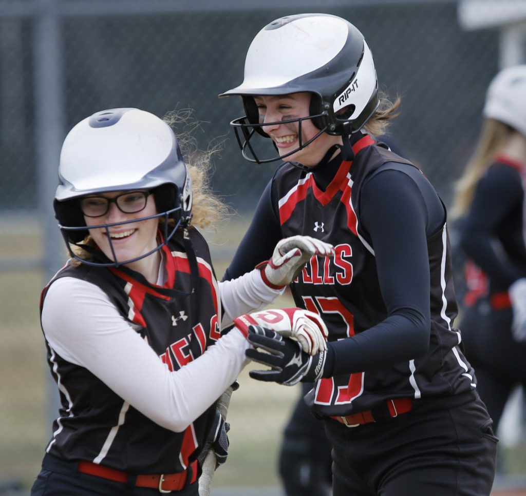 Sam Bogue of Wells, right, celebrates her three-run homer with teammate Olivia Clay in the fifth inning of a 6-0 victory against Greely to open the Western Maine Conference softball season Thursday.